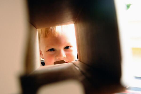Kind schaut durch die Umzugskiste