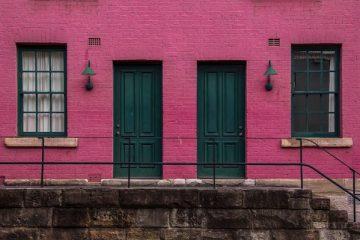 Ein pinke Hausfassade mit grünen Türen - sharing economy in der Schweiz