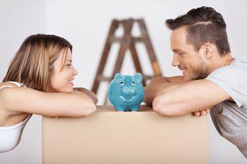 Eine junge Frau und ein Mann sind glücklich über ihre Umzugsfinanzierung